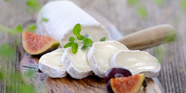 37436329 - goat cheese with figs and black olives on a wooden cutting board