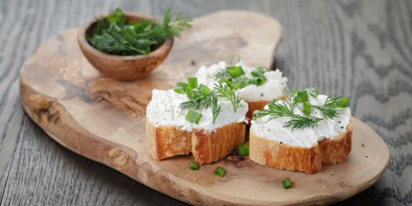 48267787 - crunchy baguette slices with cream cheese and herbs on olive board